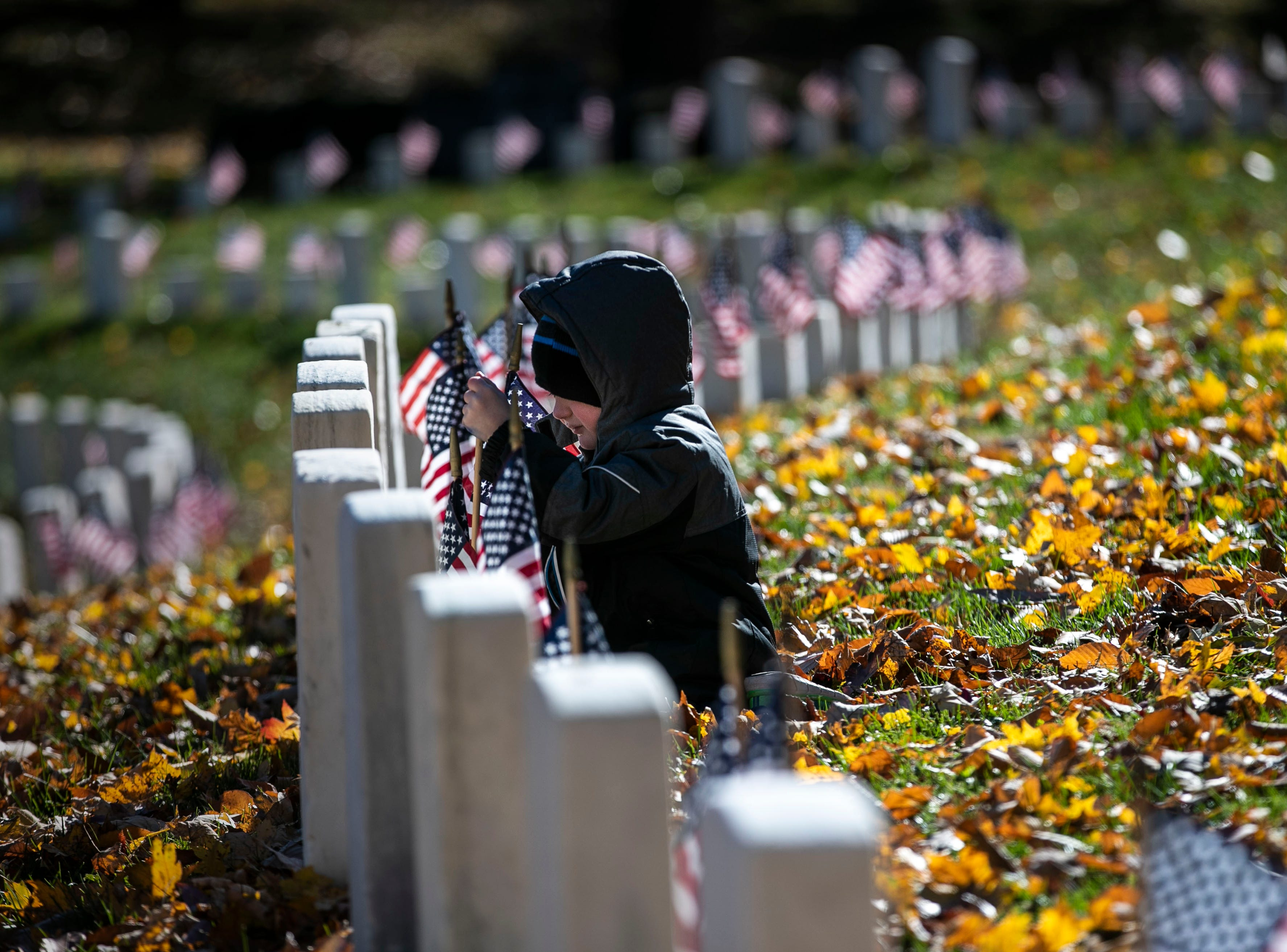 Michael Bonis, 5, finds a grave needing a small American flag during a Flags 4 Vets event at Cave Hill Cemetery Saturday, Nov. 10, 2018. Veterans Day is Sunday, Nov. 11. Around 250 volunteers placed nearly 7,500 flags on military veteran gravesites.