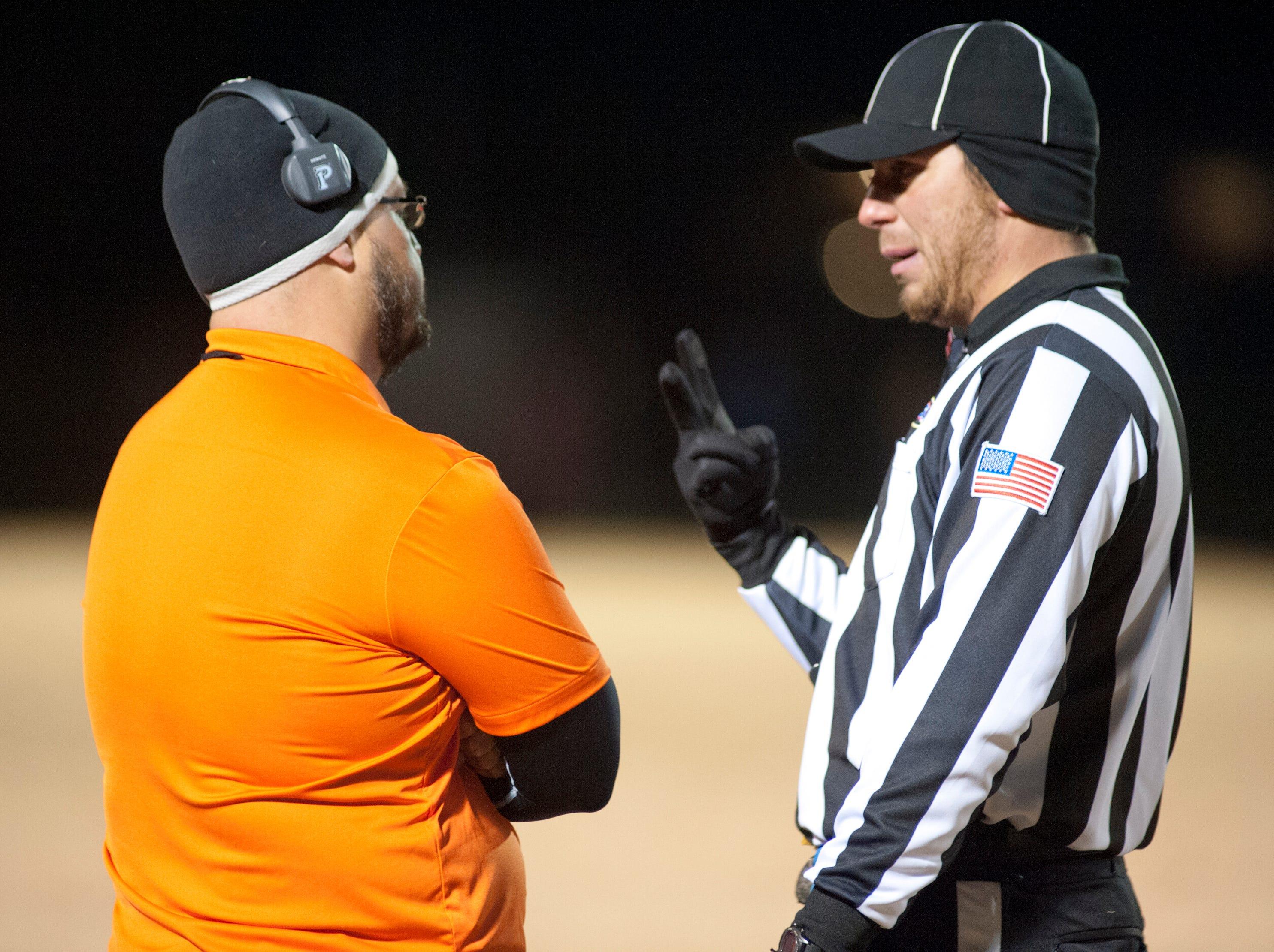 The referee explains a foul on each team to Fern Creek head football coach Joshua Abell. Nov. 9, 2018