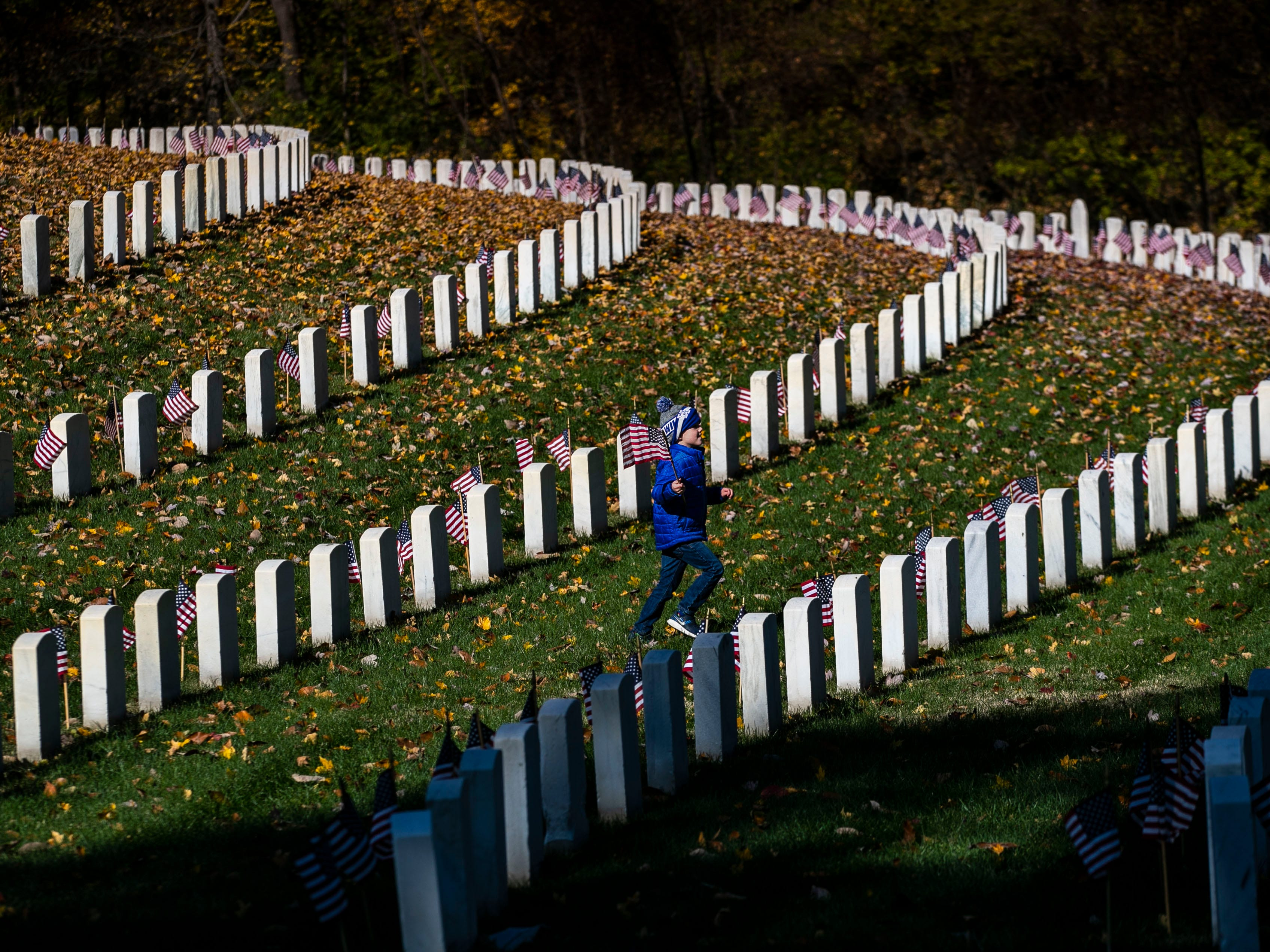 A boy carrying a small American flag runs to catch up to friends during a Flags 4 Vets event at Cave Hill Cemetery Saturday, Nov. 10, 2018. Veterans Day is Sunday, Nov. 11. Around 250 volunteers placed nearly 7,500 flags on military veteran gravesites.