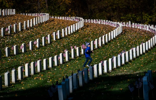 A boy carrying a small American flag runs to catch up to friends at Cave Hill Cemetery.