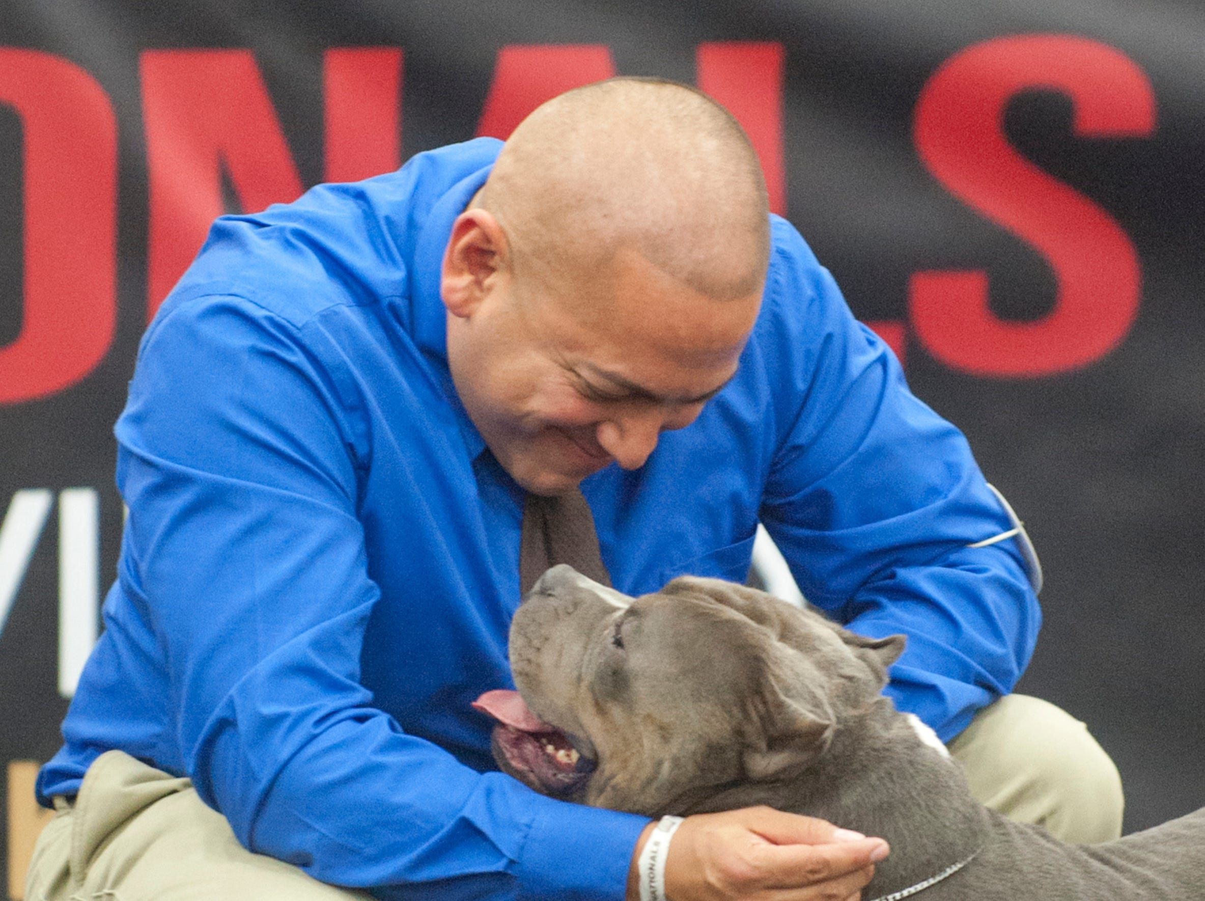 Michael Mata of Winner's Circle Kennels of Cheyenne, WY, hugs his dog Bullgari after placing 2nd in the pocket bull (ages 1-2) category during the 2018 American Bully Kennel Club's 12th annual confirmation event at the Kentucky Convention Center in Louisville.November 10, 2018