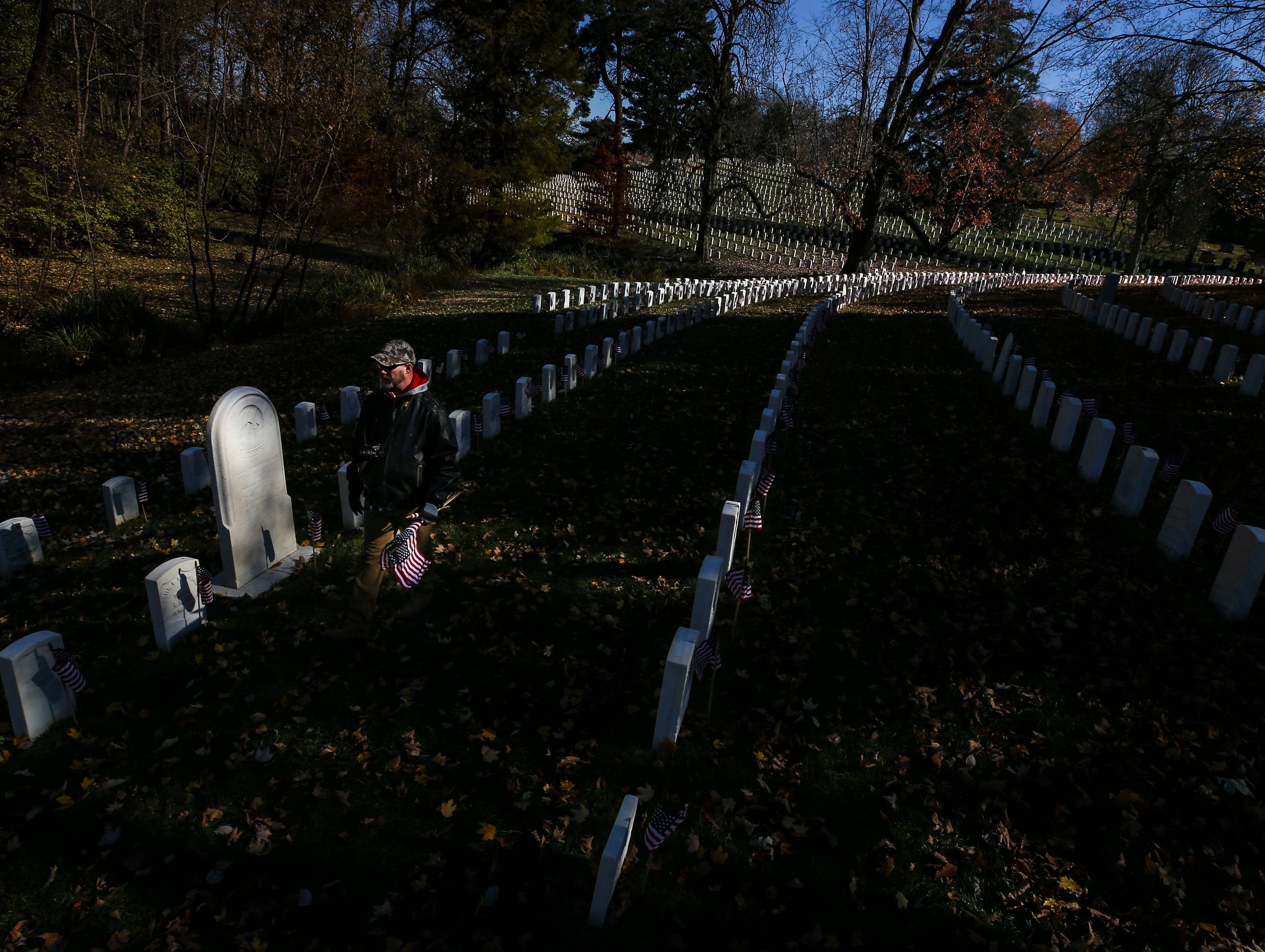 Tom Ashe, an Army veteran of seven years, walks through Cave Hill Cemetery after a Flags 4 Vets event Saturday, Nov. 10, 2018. Veterans Day is Sunday, Nov. 11. He said he comes every year and brings his two sons and wife to honor those who served.