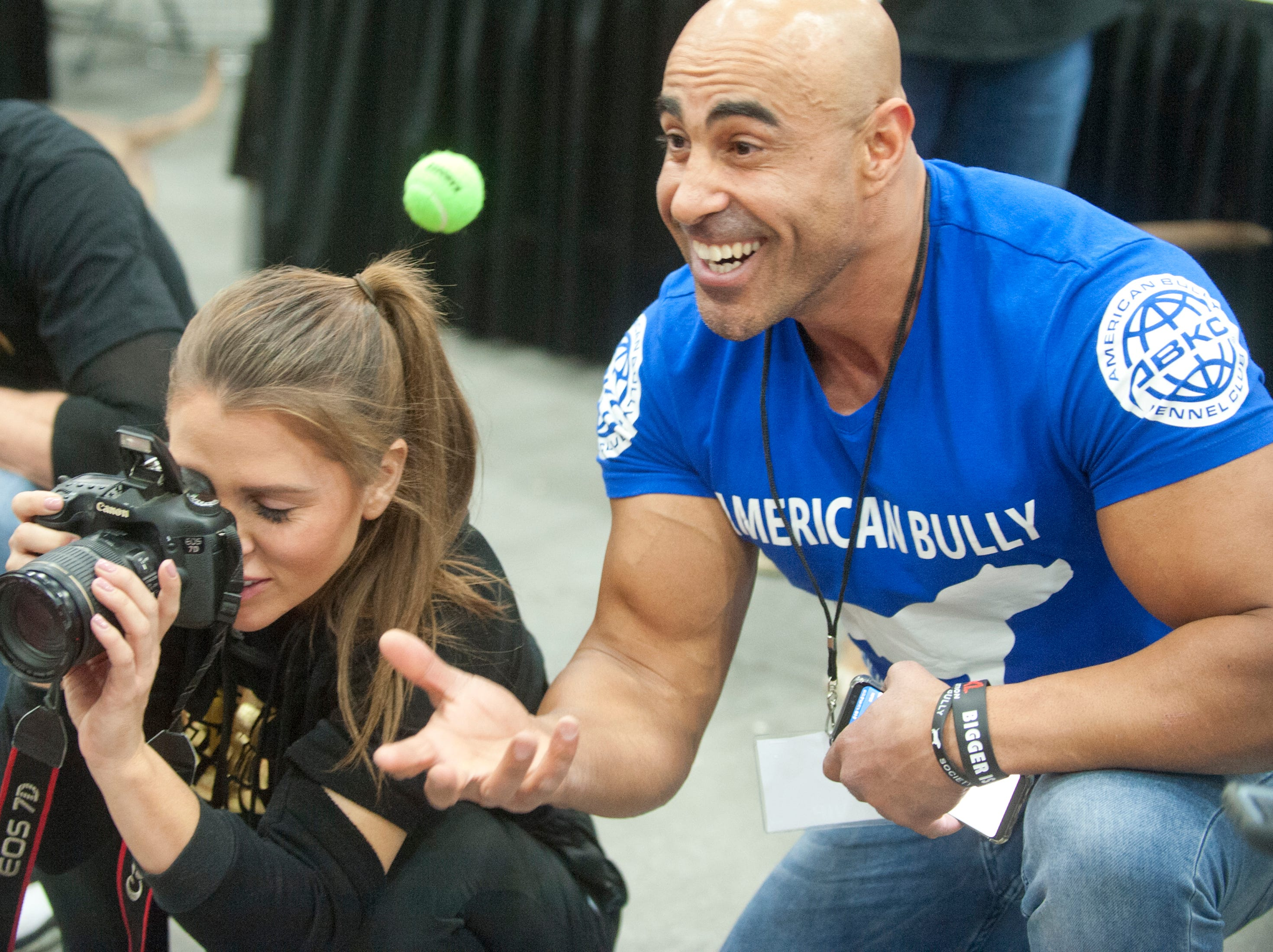 Ragim Simone Magh of the Netherlands tosses a ball in the air to get the attention of a bulldog as its owner, Kathryn Sowerbrower of Bossy Kennels, IN.c, of Marrietta, CA., snaps its portrait at the 2018 American Bully Kennel Club's 12th annual confirmation event at the Kentucky Convention Center in Louisville.November 10, 2018