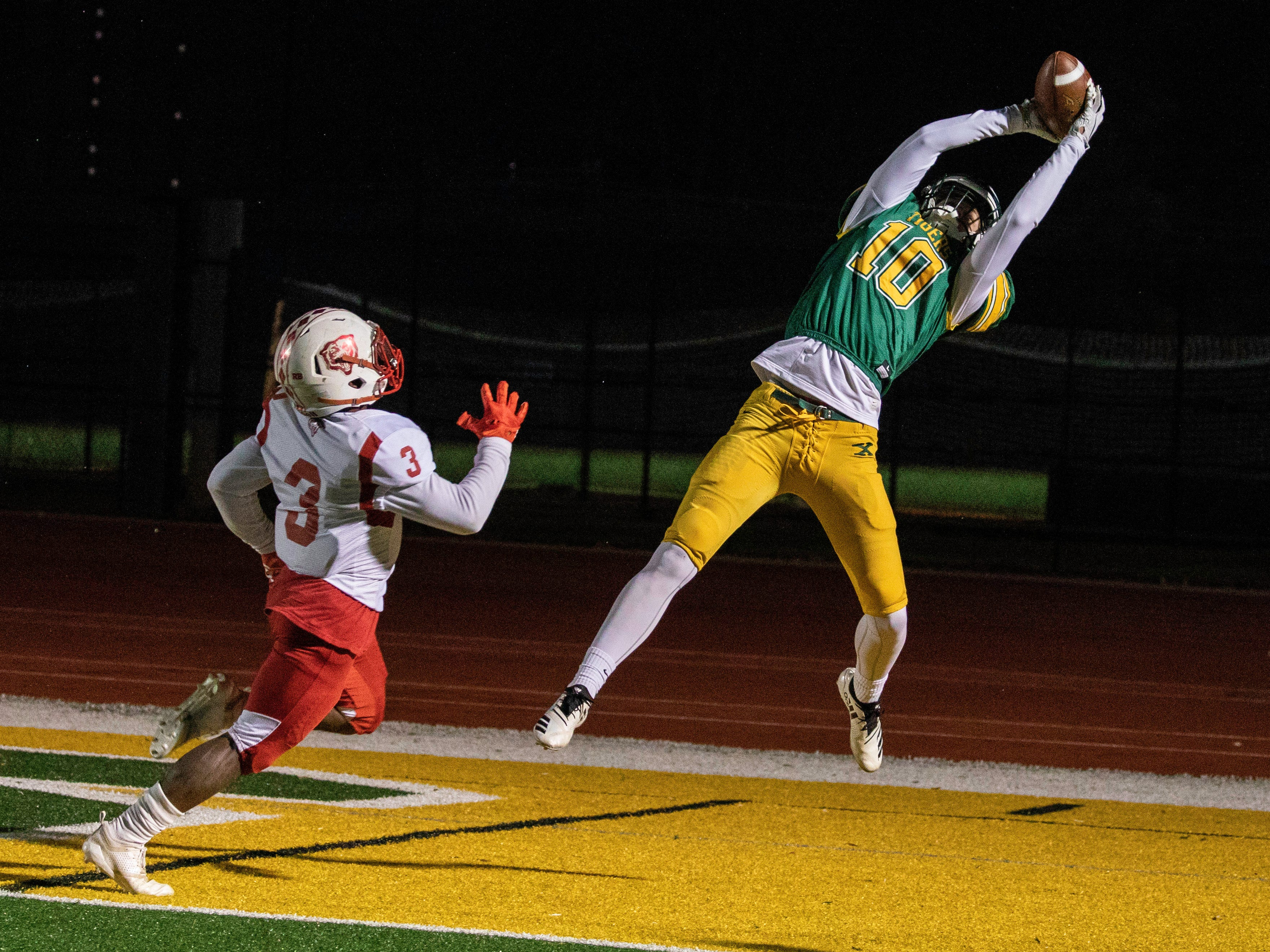 Brycen Harkins stretches out for the first touchdown of the game against Butler in the second round of the playoffs at St. Xavier High School, Friday, Nov. 9, 2018.