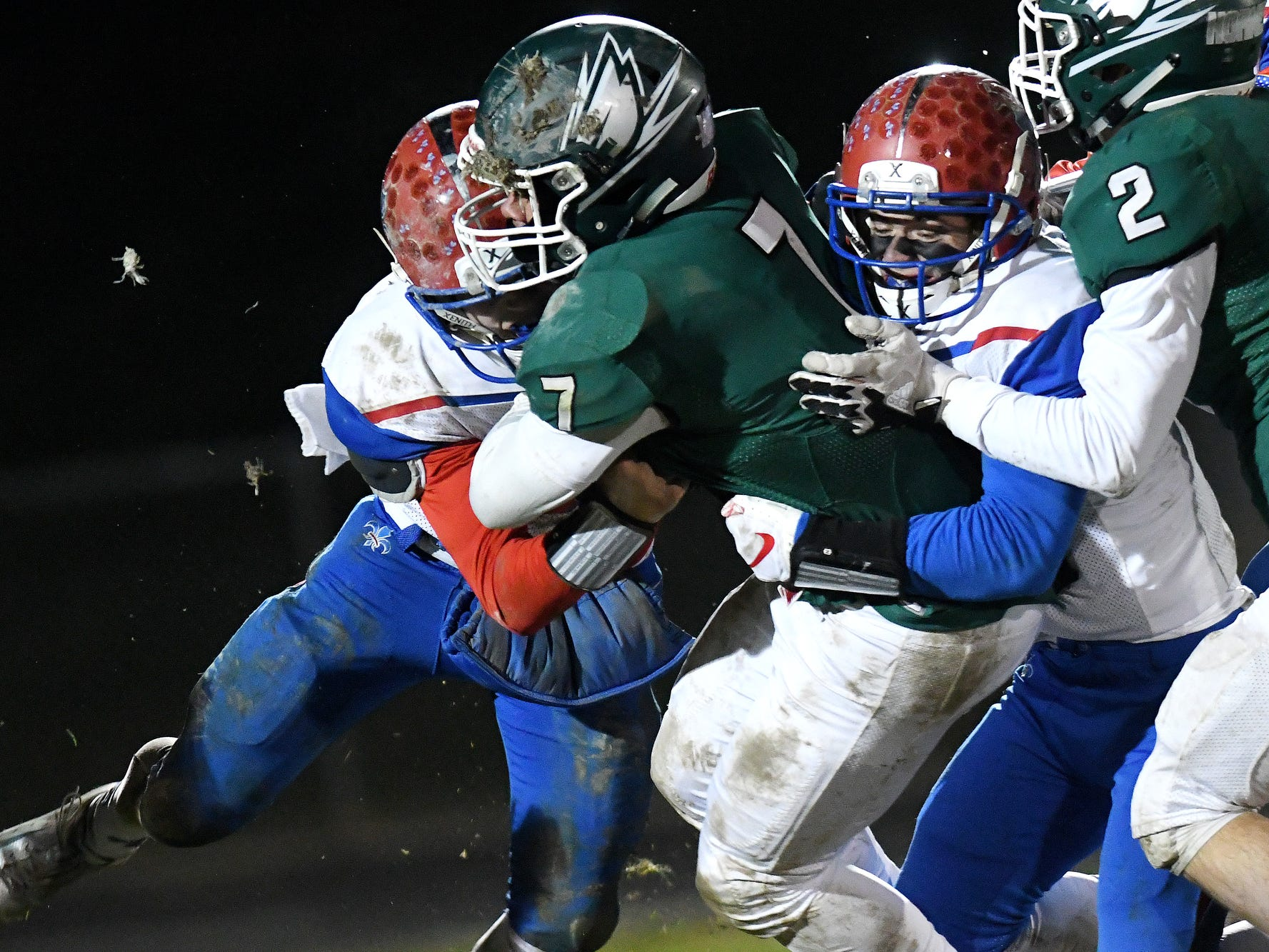 Williamston's Evan Field, center, runs for a gain as St. Clair defenders close in during the fourth quarter on Friday, Nov. 9, 2018, in Williamston.