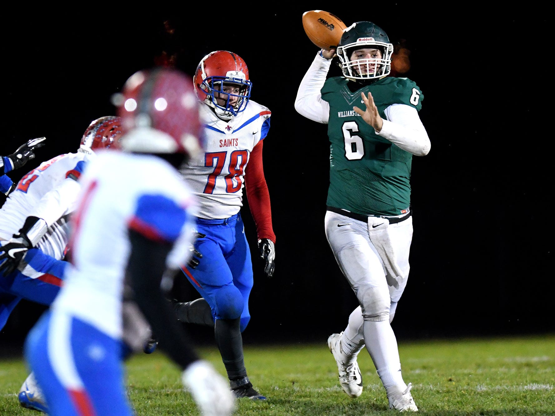 Williamston's Austin Stiffler, right, throws a touchdown pass to Carey Haney as St. Clair's Lance Schweihofer closes in during the first quarter on Friday, Nov. 9, 2018, in Williamston.