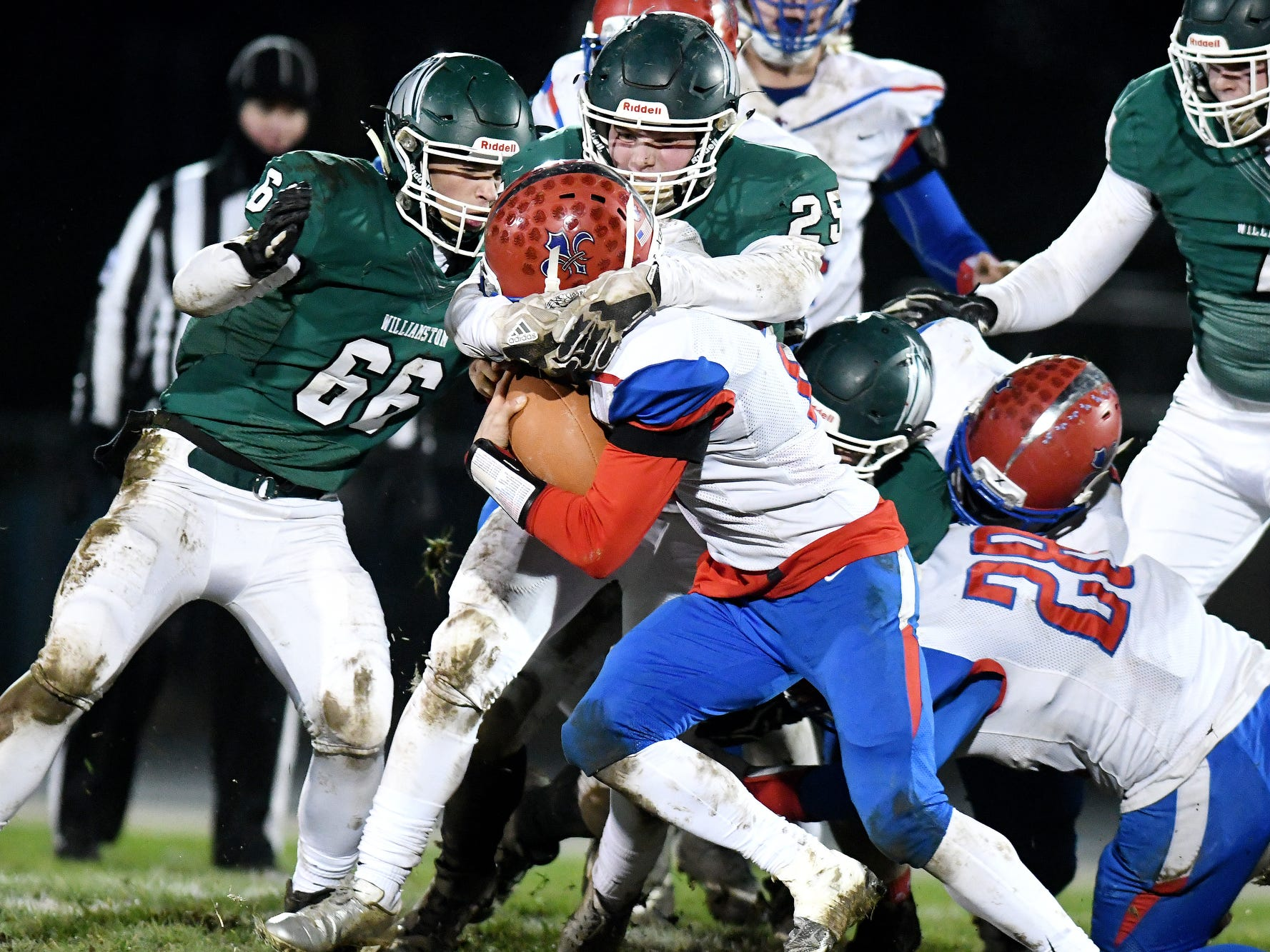 Williamston's Conner Sparks, right, and Jacob Jones, left, tackle St. Clair's Ethan Mahn during the second quarter on Friday, Nov. 9, 2018, in Williamston.