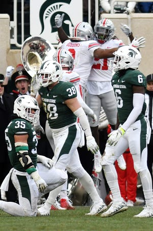 From left, Michigan State's Joe Bachie, Byron Bullough and David Dowell look on Ohio State's Parris Campbell Jr. celebrates his touchdown run the the background during the second quarter on Saturday, Nov. 10, 2018, in East Lansing.