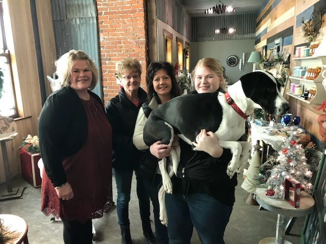 Sabrina Krejci holds her dog jet with her mom Mandy and local community members who helped her open her store.