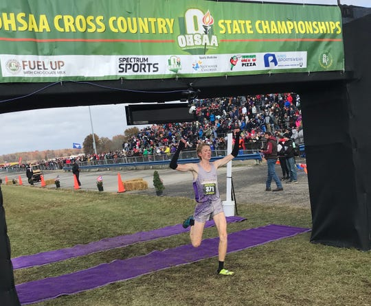 Lexington's Kyle Johnston raises his arms as he crosses the finish line in first place on Saturday at the state cross country championships at National Trail Raceway in Hebron.