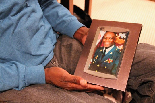 Gulf War veteran Richard Young holds a picture of his younger self in the basement of his Marion home on Monday. The native of Louisiana joined the Army right out of High School in 1974. He reenlisted following a brief stint back into civilian life in 1977 and stayed in its ranks before retiring in 1998.