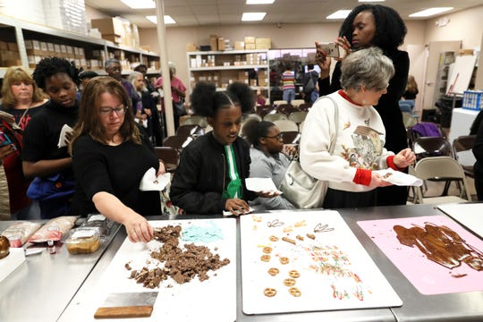 Class participants grab pieces of sweets created at Mary Carter Decorating Center's Holiday Candy Class on Saturday, Nov. 10, 2018.