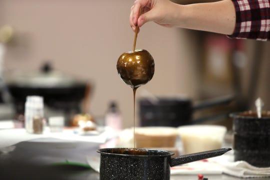 Toni Faherty prepares a hard candy-coated apple.