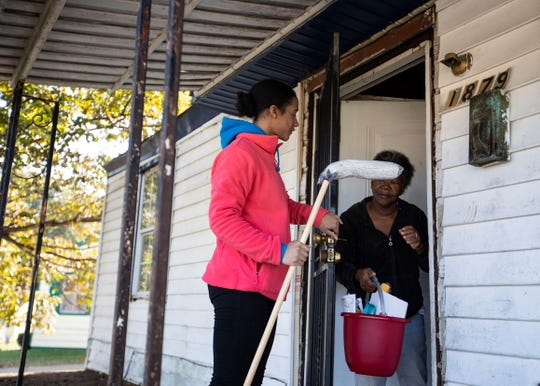 Habitat for Humanity of Greater Memphis volunteer, Britni Collins, gives a Castalia Heights resident flowers and a cleaning supply kit Saturday.