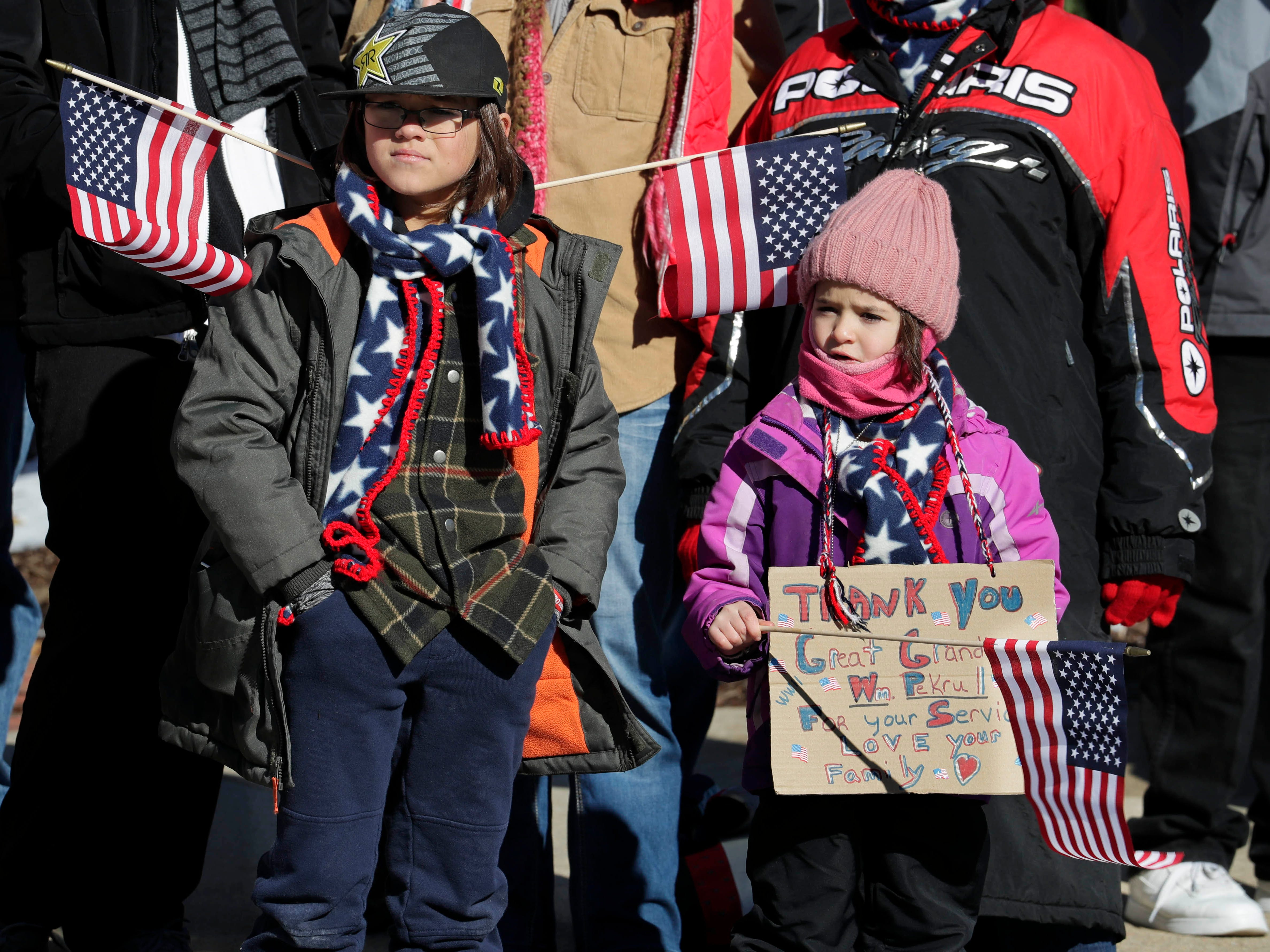 Henry Labarge, 11, and Ella Lein, 6, show their support for veterans as they braved cold temperatures to watch the Milwaukee Veterans Day parade Saturday.