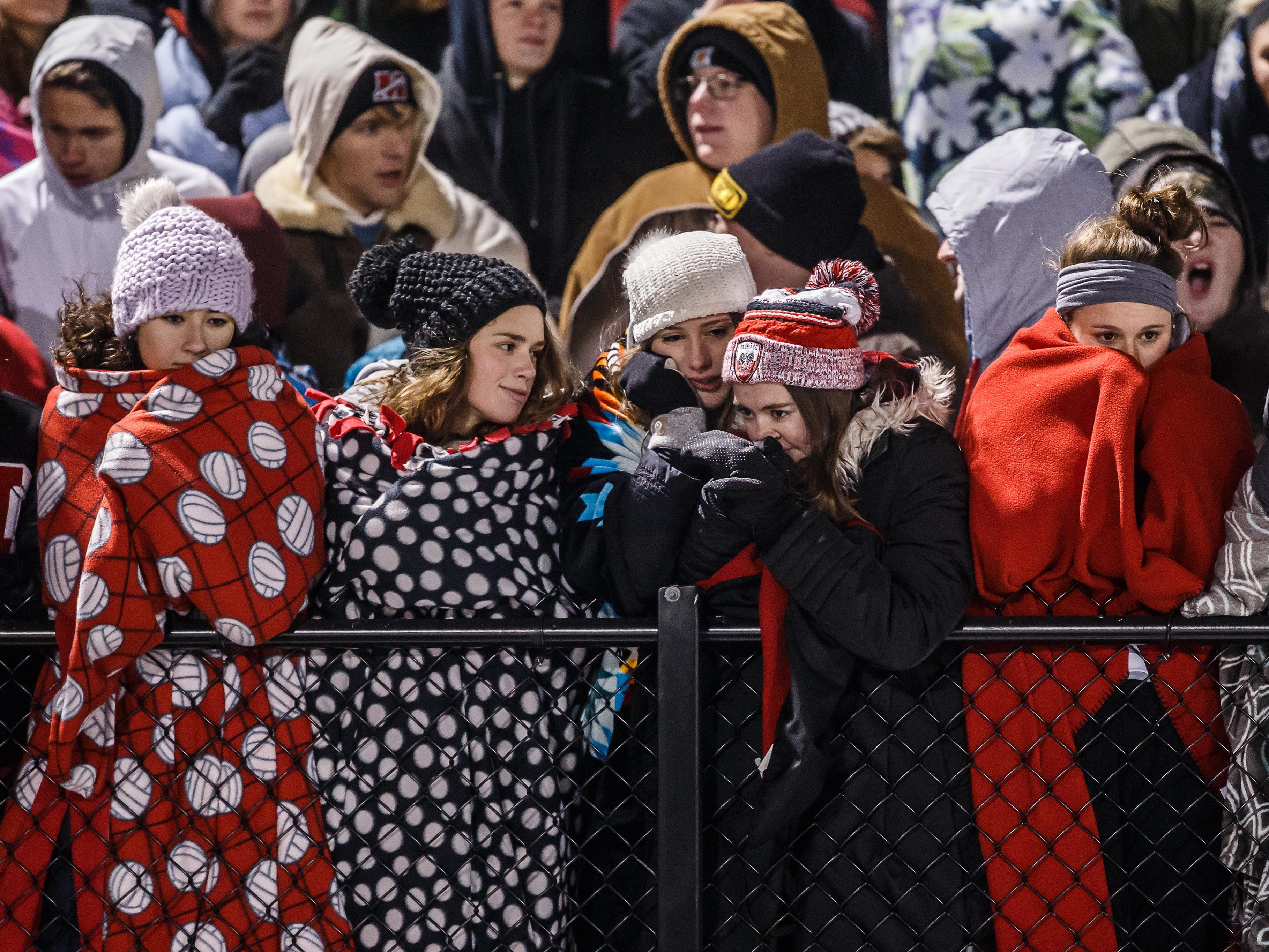 Muskego students brace against a single digit wind-chill during the WIAA Division 1 Level 4 playoff game against Marquette in Hartland on Friday, Nov. 9, 2018.