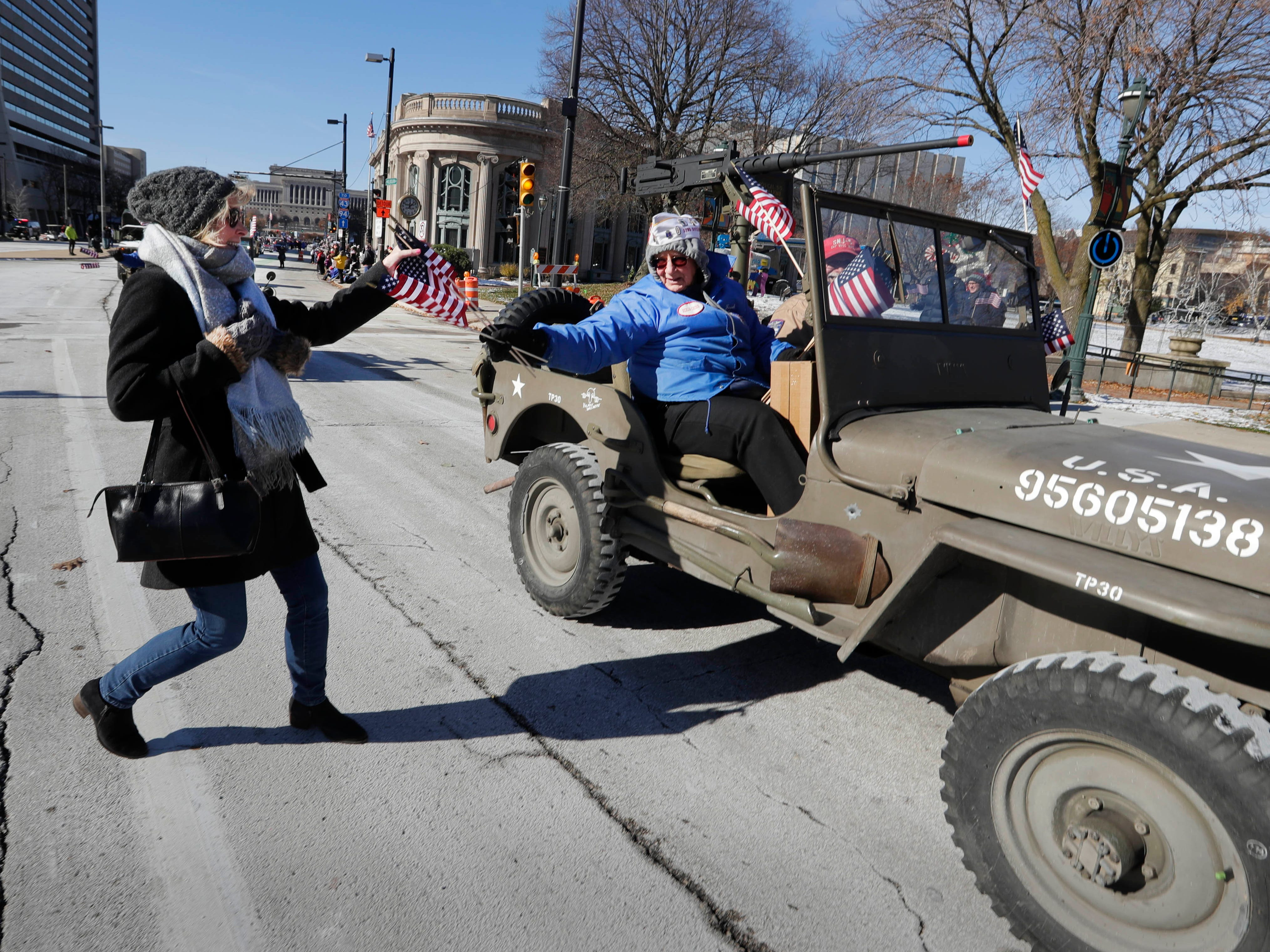 Aisling Maglio of Muskego, receives one of many flags handed out by veteran organizations during the parade.