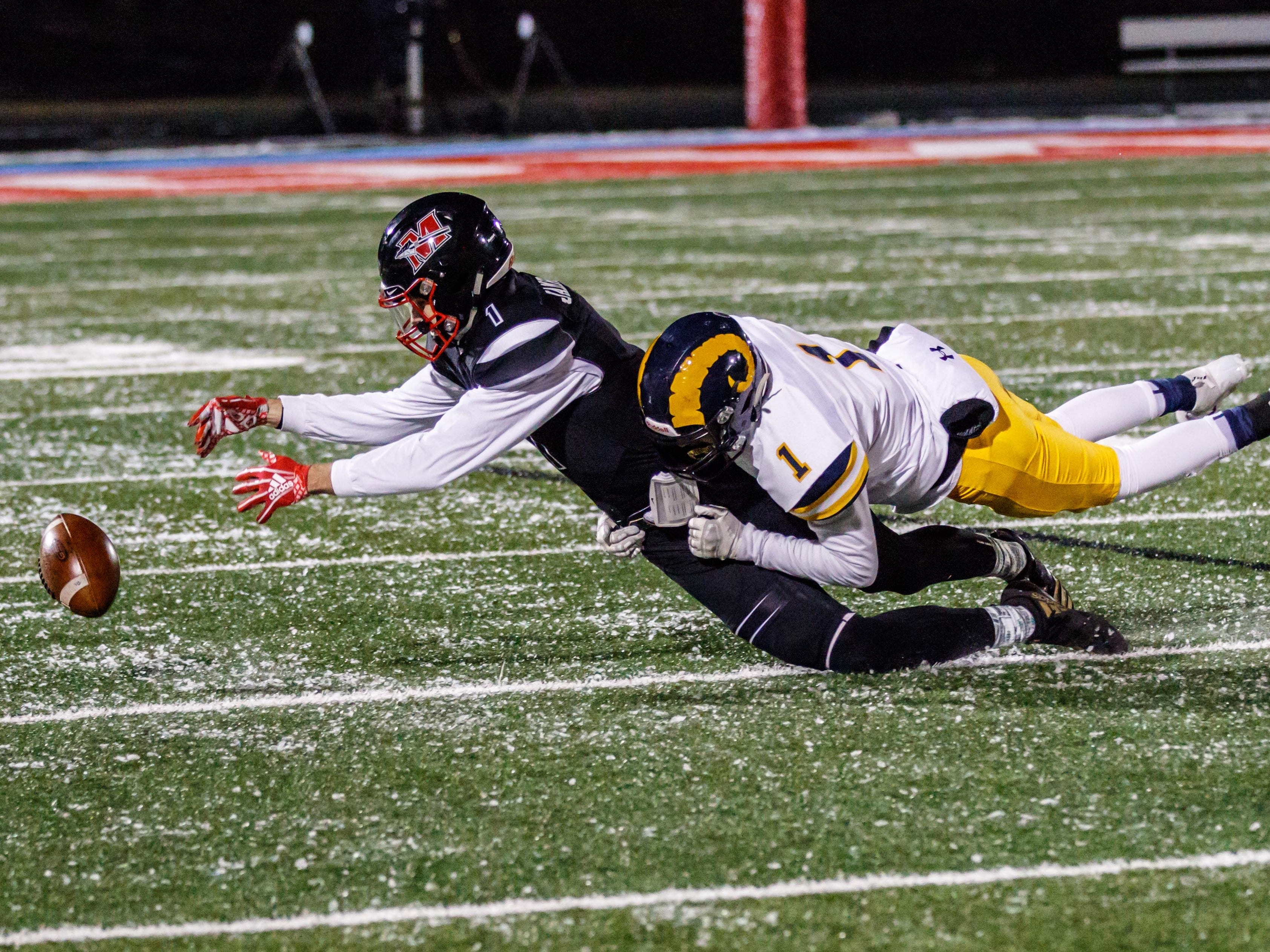 Marquette defensive back Patrick Coury (right) causes Muskego's Steven Jamroziak to drop a pass during the WIAA Division 1 Level 4 playoff game against Muskego in Hartland on Friday, Nov. 9, 2018.
