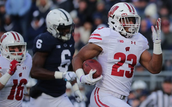 Wisconsin running back Jonathan Taylor runs away from Penn State defenders as he scores from 71 yards out on Saturday.