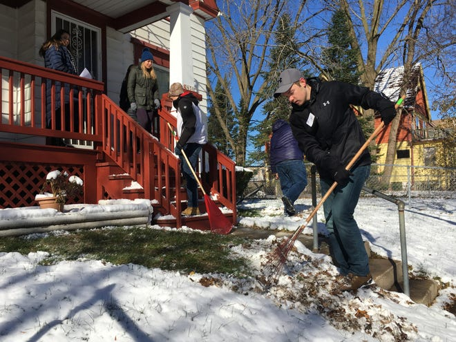 """Zac Beine, a Marquette University freshman from Watertown, rakes leaves Saturday as part of Marquette's """"Make a Difference Day"""" in Milwaukee"""