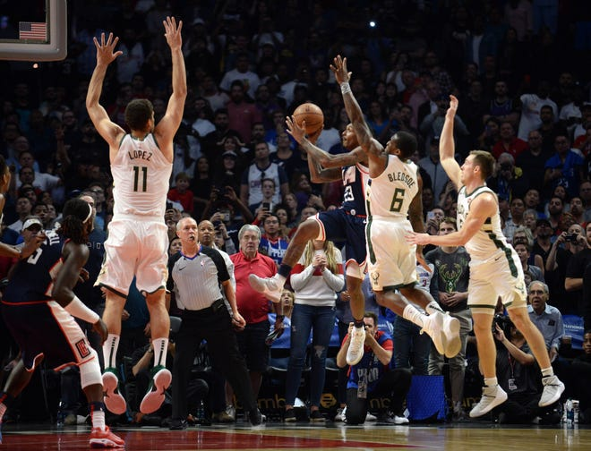 Clippers guard Lou Williams gets past Bucks guards Eric Bledsoe and Pat Connaughton and shoots over Brook Lopez as he hits the winning bucket in overtime on Saturday.