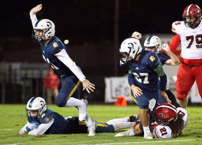 St. James's Alex Whisenhunt recovers a fumbled ball by T.R. Miller's Dairus Webb as his teammates celebrate around him.