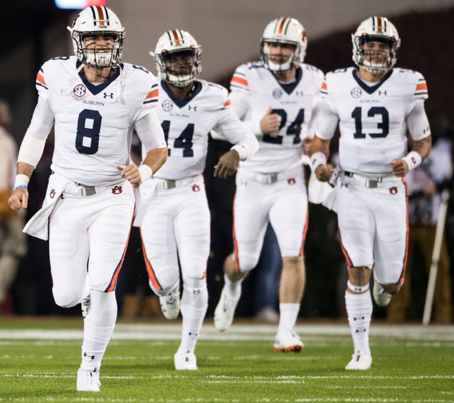 Jarrett Stidham (8) leads Auburn quarterbacks Malik Willis (14), Cord Sandberg (24) and Joey Gatewood (13) onto the field for warm ups before taking on Georgia at Sanford Stadium in Athens, Ga., on Saturday, Nov. 10, 2018.