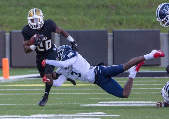 Jackson State's CJ Holmes grabs ahold of Alabama State's Ezra Gray as he runs the ball during a play in the first quarter.