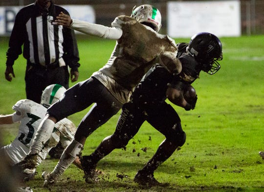 Catholic's Darrell Gibson avoids a tackle after Holtville's Jadarius Carter slips on the muddy field.