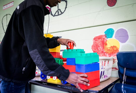 Kory Jones spends time at an activity table listening to music while waiting for a class to start at Hillcroft Services.