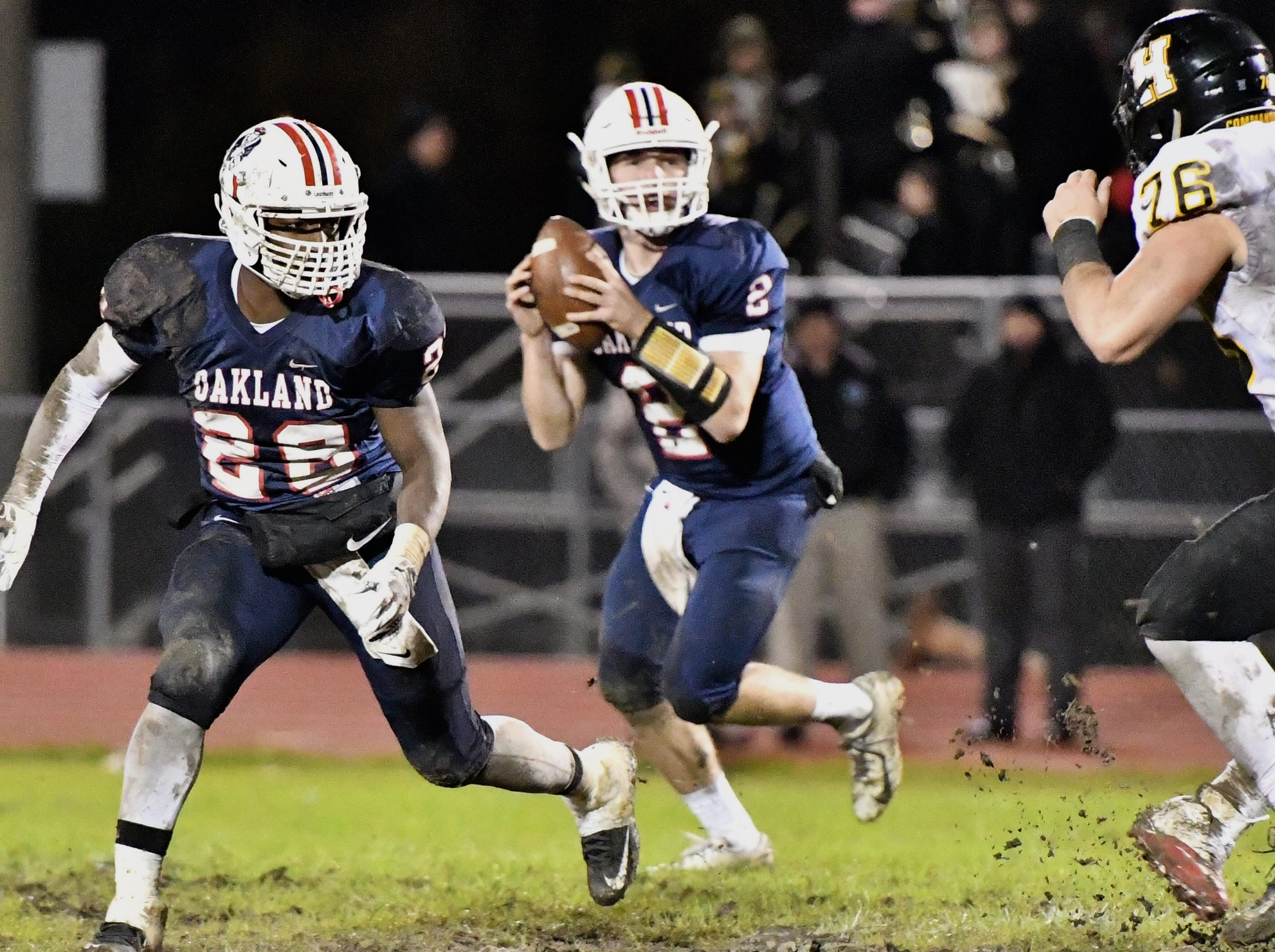 Oakland's Brevin Linnell drops back to pass Friday night as teammate Xavier Myers prepares to block HHS' Wilson Higgs.