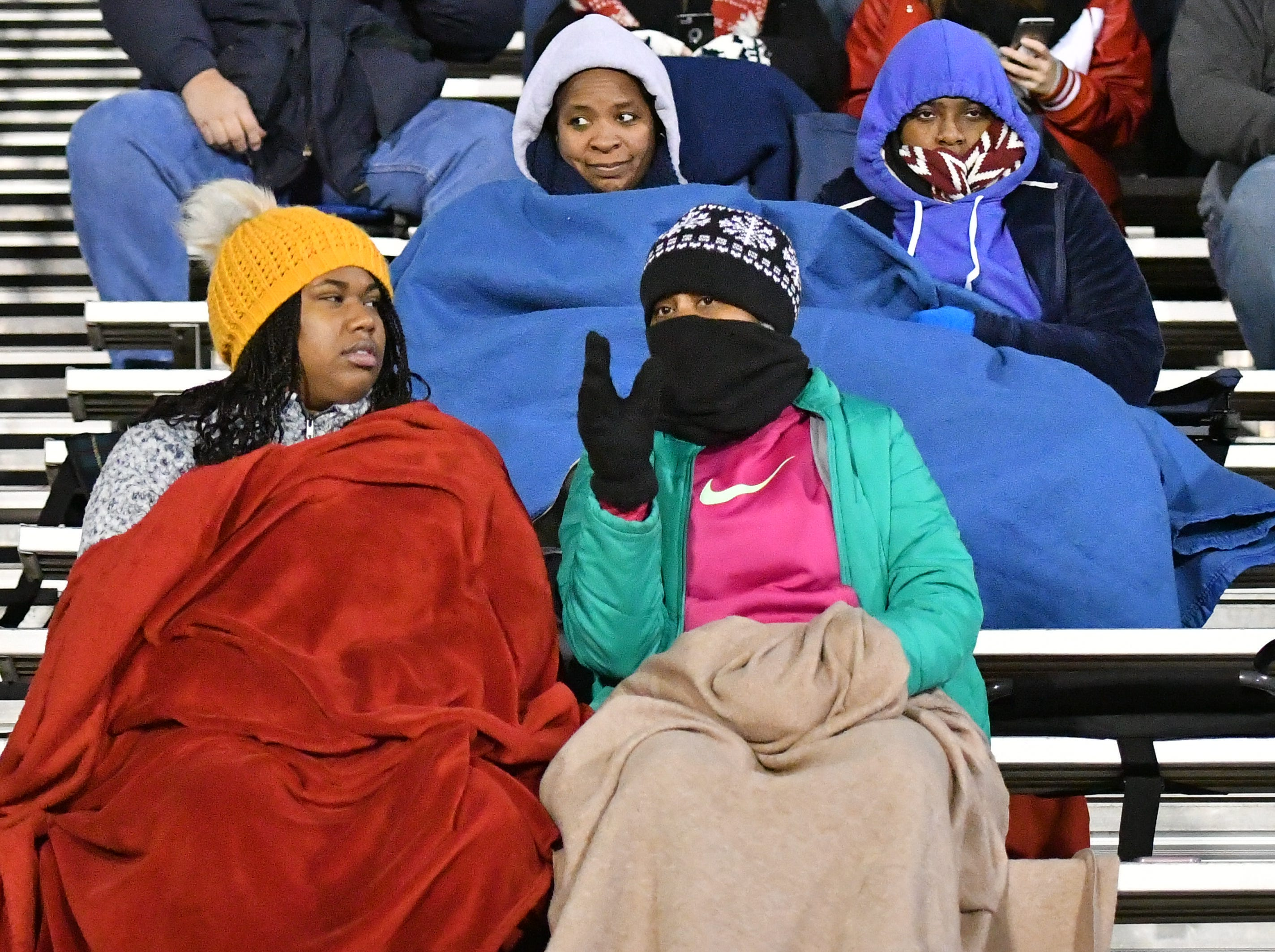 Oakland fans try to stay warm during their game with Hendersonville Friday night.