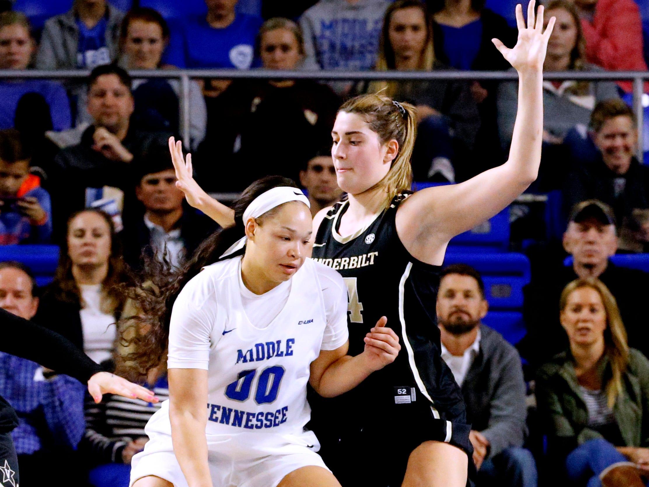 MTSU's Alex Johnson (00) pushes to the basket as Vanderbilt's Mariella Fasoula (34) guards her during the women's home opening game at MTSU on Friday, Nov. 8, 2018.