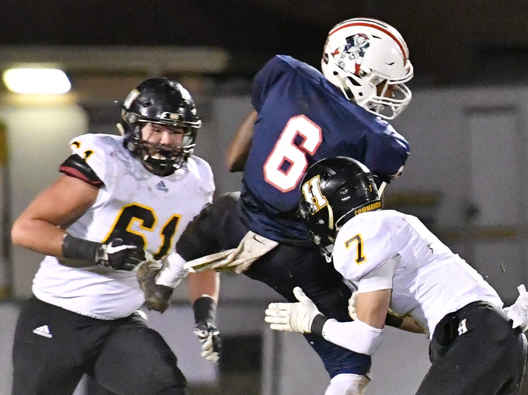 Oakland receiver Justin Jefferson hauls in a pass against Hendersonville Friday night as Logan Spurrier and Zach Rockom move in for the tackle.