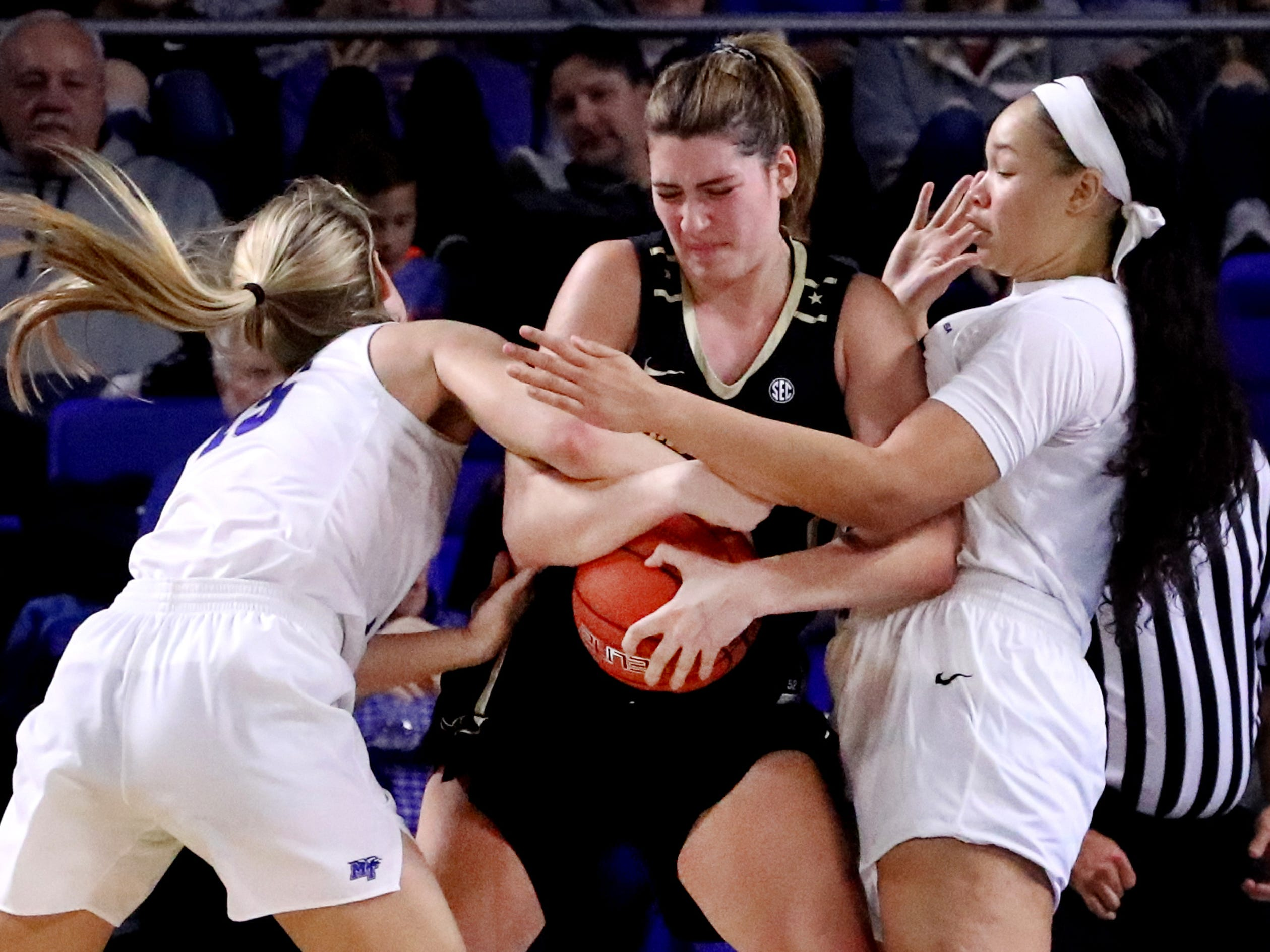 MTSU's Anna Jones (15) tries to steal the ball from Vanderbilt's Mariell Fasoula (34) as MTSU's Alex Johnson's (00) guards Fasoula during MTSU women's home opening game at MTSU on Friday, Nov. 8, 2018.