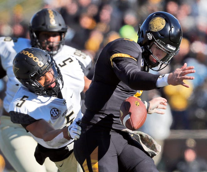 Missouri quarterback Drew Lock, right, fumbles as he is hit by Vanderbilt safety LaDarius Wiley during the first half of an NCAA college football game Saturday, Nov. 10, 2018, in Columbia, Mo. Lock recovered the fumble.