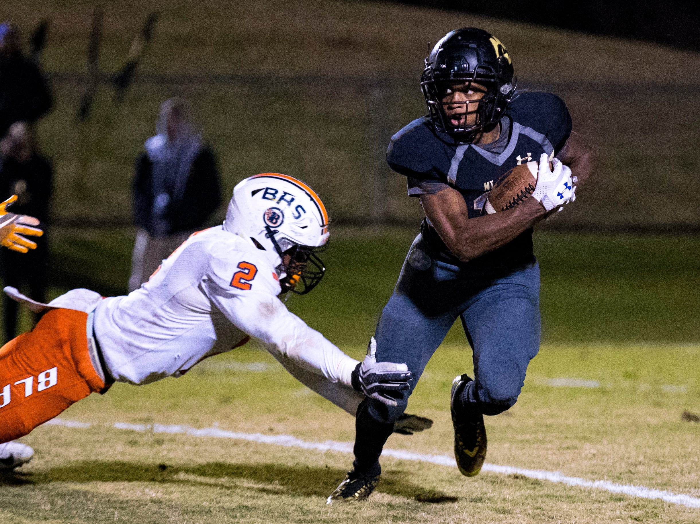 Mt. Juliet's Colby Martin (11) dodges a tackle from Blackman's Khori Williams (2) during Mt. Juliet's game against Blackman at Mt. Juliet High School in Mt. Juliet on Friday, Nov. 9, 2018.