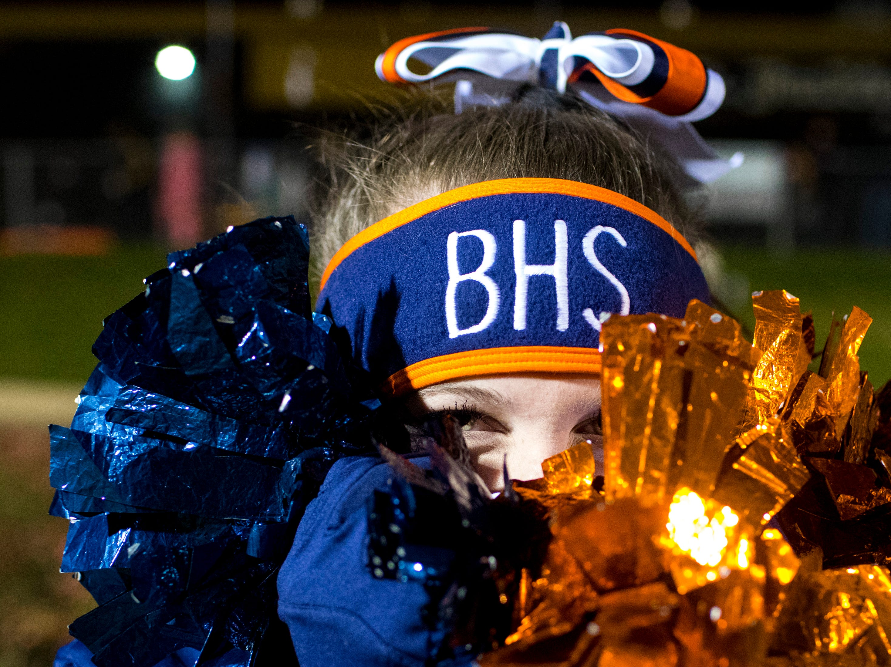Blackman's cheerleader Lindsay Abernathy uses her pompoms to cover her face because she said she was cold before Mt. Juliet's game against Blackman at Mt. Juliet High School in Mt. Juliet on Friday, Nov. 9, 2018.