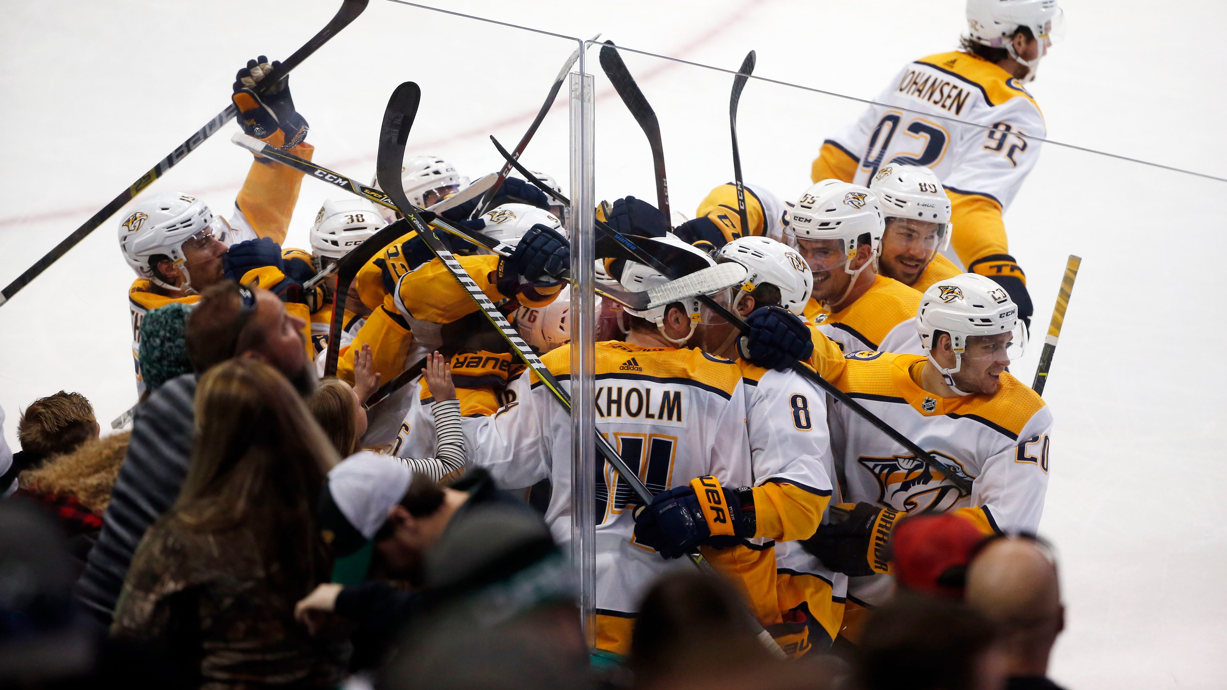 Nashville Predators defenseman Mattias Ekholm (14) is swarmed by teammates after his game-winning goal against the Dallas Stars during overtime of an NHL hockey game in Dallas, Saturday, Nov. 10, 2018.