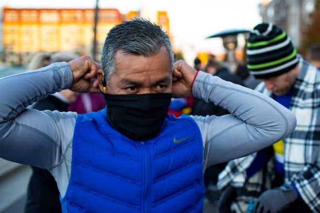 Edgar Flores puts on his face mask before the Nashville Half Marathon, Marathon & 5K in Nashville on Saturday.