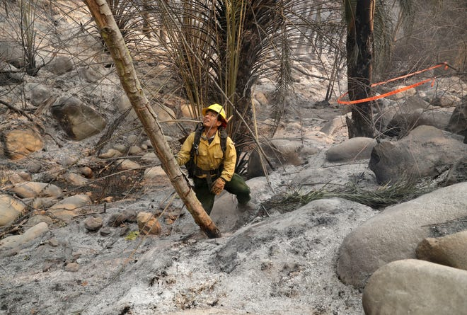 Firefighter Eric Santana, with the MRCA Fire Divison Santa Monica Mountains, looks for hot spots after a wildfire swept through Saturday, Nov. 10, 2018, in Malibu, Calif.