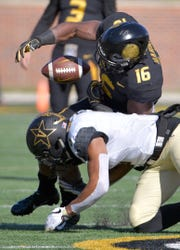 Tigers running back Damarea Crockett (16) fumbles the ball as he is tackled by Vanderbilt Commodores safety LaDarius Wiley (5) during the first half at Memorial Stadium/Faurot Field.