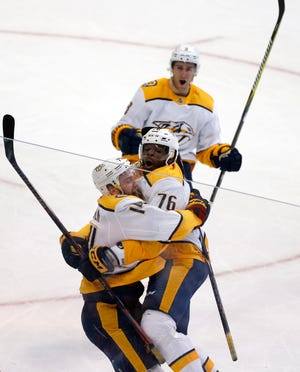 Predators defenseman Mattias Ekholm (14) celebrates his game-winning goal in overtime Saturday against the Stars with defenseman P.K. Subban (76) and center Kyle Turris (8).