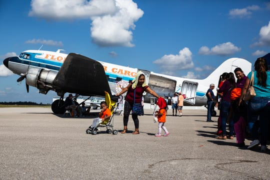 A family departs after collecting their bag of goodies from the sixth annual Turkeys Take Flight event on Nov. 10, 2018, at the Immokalee Regional Airport. The event provided families in need with a frozen turkey and fixings. The food arrived in a vintage DC-3 aircraft, an aircraft used during World War II.