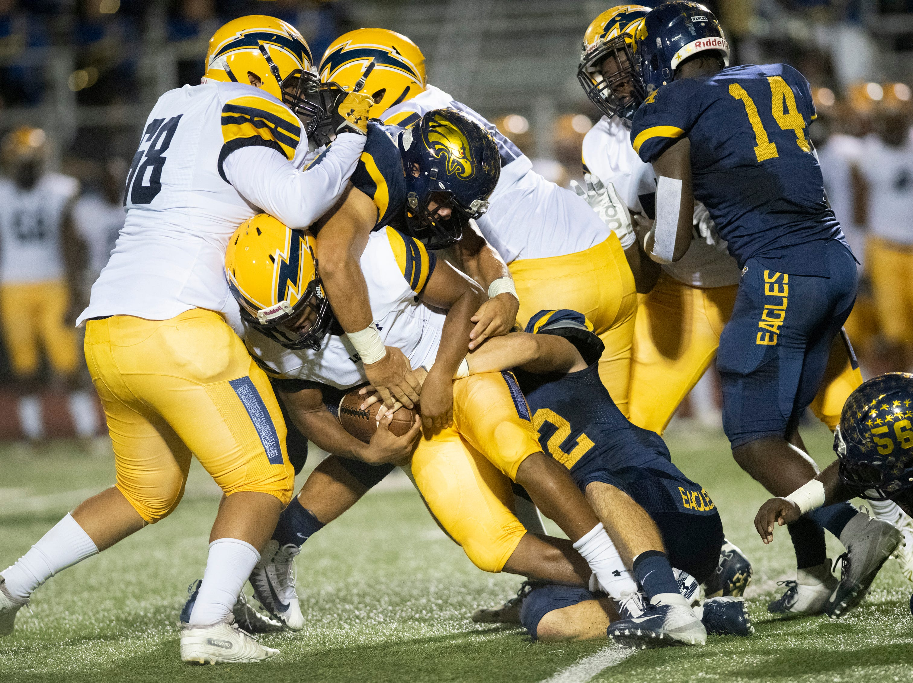 Bud Chaney of Lehigh is tackled by Naples defenders during the Class 6A regional quarterfinal playoff game at Naples High on Friday night, November 9, 2018.