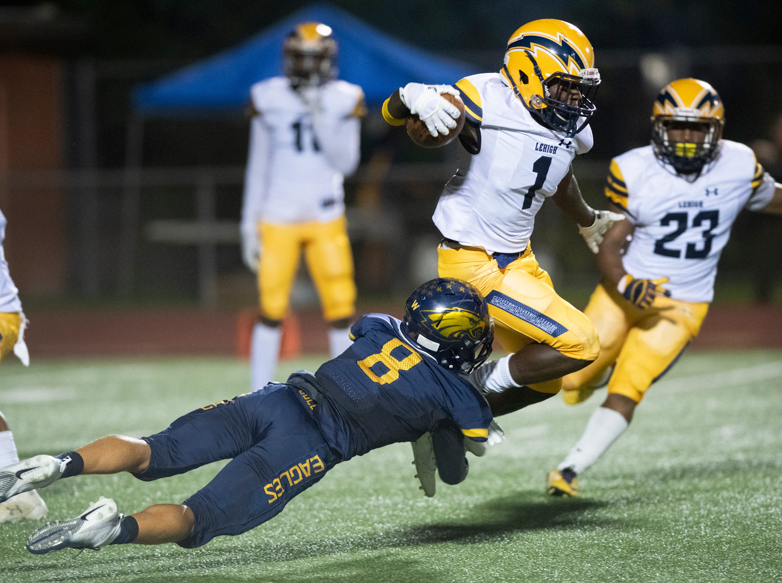 Al'Jarius Kelly of Lehigh is tackled by Tre Smith of Naples as he runs with the ball during the Class 6A regional quarterfinal playoff game at Naples High on Friday night, November 9, 2018.