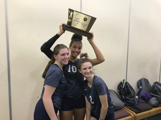 IHA volleyball players (from left) Lizzy Patterson, Sydney Taylor and Maeve Duffin with the trophy after their team won the Non-Public championship Saturday at the William Paterson Rec Center.