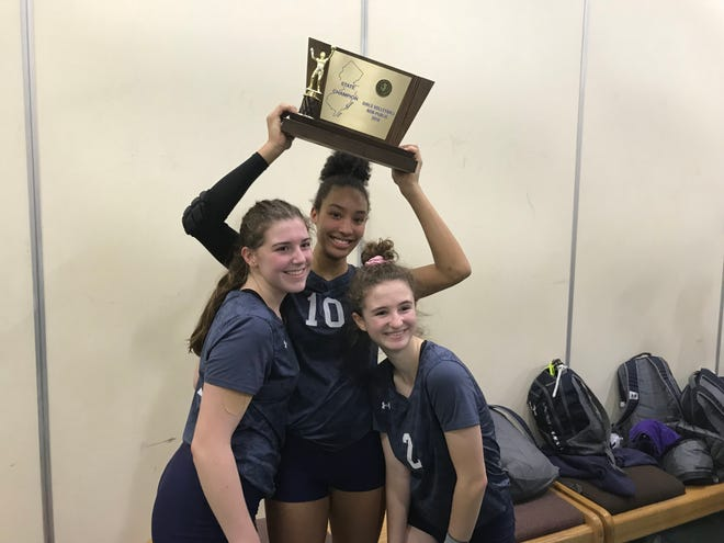 IHA volleyball players (from left) Lizzy Patterson, Sydney Taylor and Maeve Duffin with the trophy after their team won the Non-Public championship on Saturday, Nov. 10, 2018 at the William Paterson Rec Center.