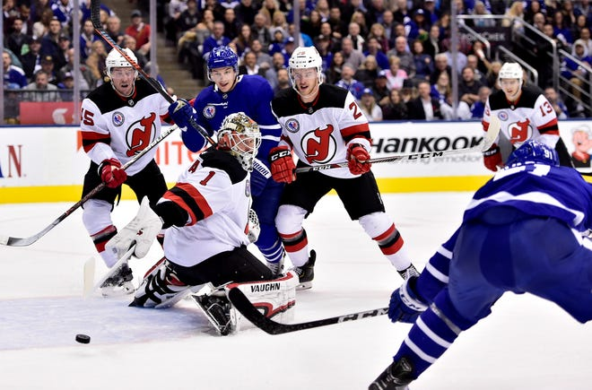 Toronto Maple Leafs center John Tavares, right front, shoots the puck past New Jersey Devils goaltender Keith Kinkaid (1) during the first period of an NHL hockey game Friday, Nov. 9, 2018, in Toronto. Devils defenseman Sami Vatanen (45), Maple Leafs left wing Zach Hyman (11) and Devils defenseman Damon Severson (28) watch.