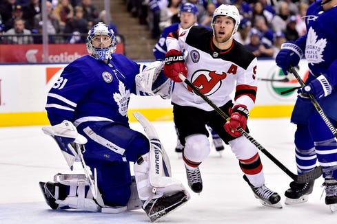 Toronto Maple Leafs goaltender Frederik Andersen (31) and New Jersey Devils left wing Taylor Hall (9) look for the puck during the second period of an NHL hockey game Friday, Nov. 9, 2018, in Toronto.
